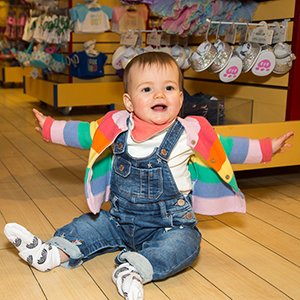 Cheerful baby wearing a colourful stripy cardigan