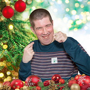 Cheerful young man surrounded by Christmas baubles
