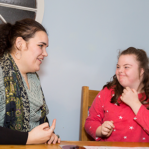 Young woman talking with a teenage girl, who has Down's syndrome